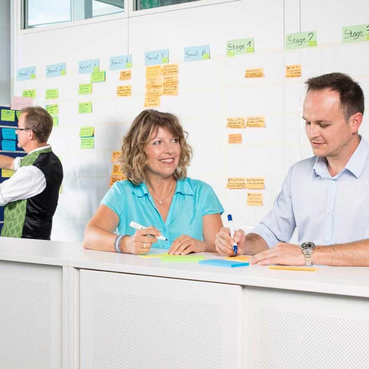 Truma employees in front of a scrum board
