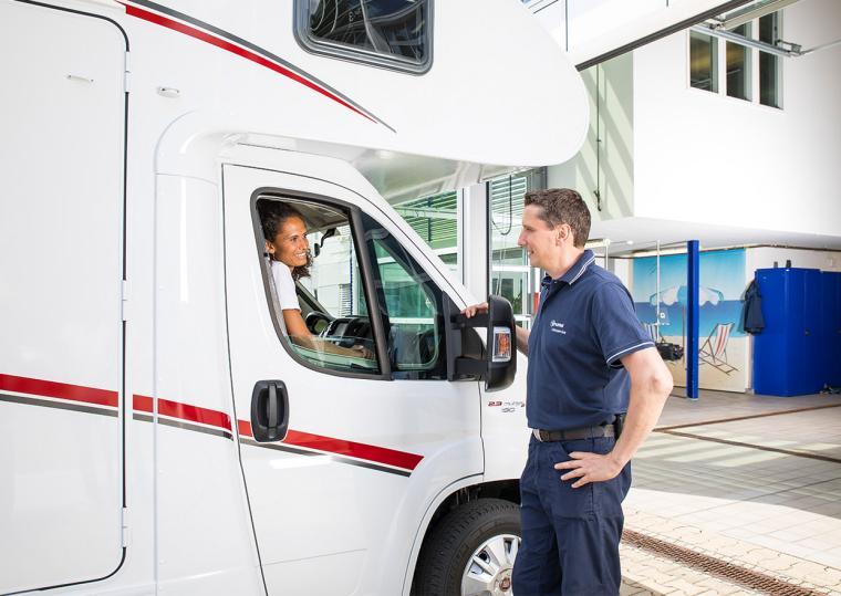 Truma employee talking to a woman in a motor caravan in the Truma service workshop